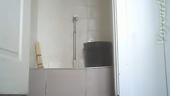 White lady in black coat and pants pisses in the toilet room