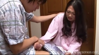 An Asian wife in her pajamas gives a sloppy handjob