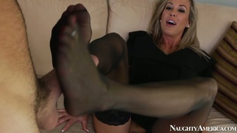 Perverted housewife in pantyhose Brandi Love provides a dude with a footjob