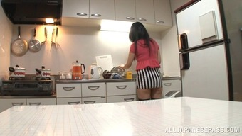 Lustful Asian cougar in miniskirt fondling her big tits before masturbating wildly in the kitchen