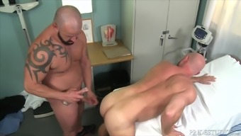 Fat tattooed gay doctor pounds his patient on the table
