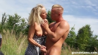 Mature blonde doggy fucked outdoors wearing a dress